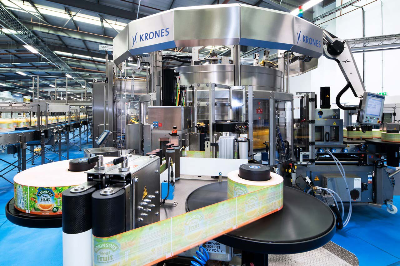 The CSD line comprises a Topmodul which is dressing the bottles with wrap-around labels.