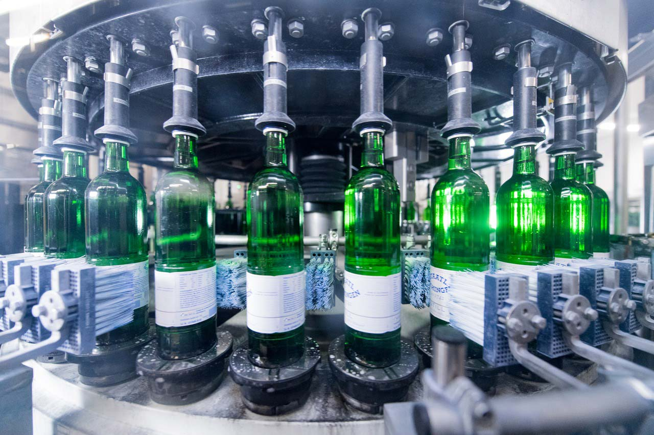 Using a servo-controlled bottle alignment device ensures that the paper labels are invariably applied to the Gourmet bottles at precisely the same place.