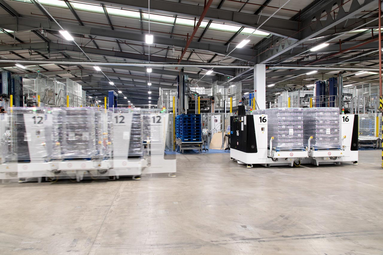 The finished cases are stored fully automatically: four pallets at a time are loaded from the line onto a large laser-guided vehicle (LGV) and taken to the ingress point of the shuttle vehicle loop, which links the production zone to the logistics halls.