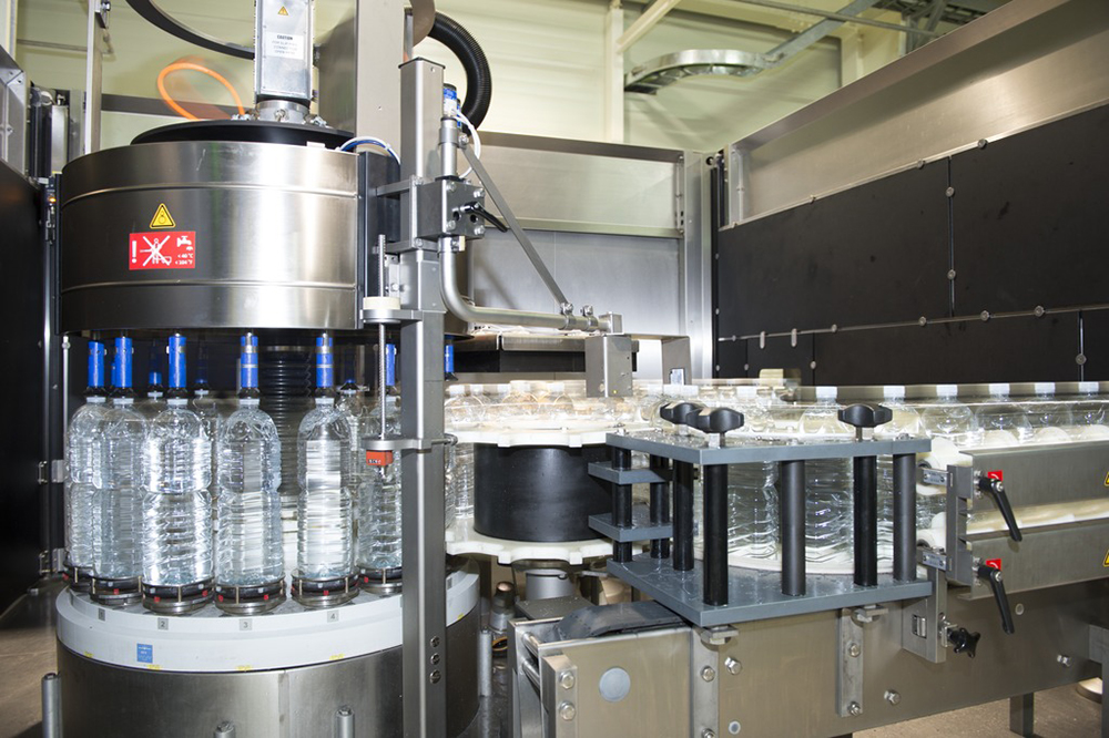 A full-bottle inspector monitors the filled PET bottles for unwanted constituents in the product, and verifies the fill level again.