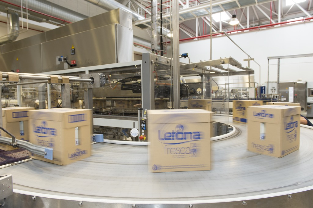 A Variopac Pro WT forms full-size cartons holding six bottles of milk in the 1-litre and 1.5-litre sizes, plus open 21-bottle trays without film for 1-litre bottles of cocoa.